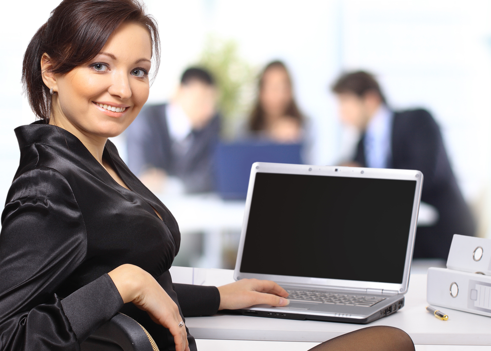 Business woman with team working on laptop