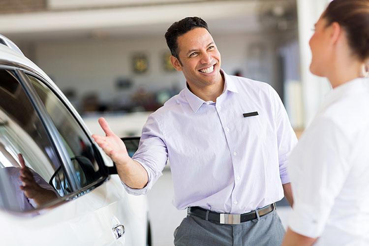 car sales representative presenting a car to customer